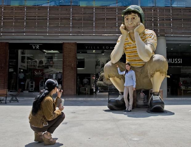 Mulher tira foto ao lado de 'Chaves' gigante em shopping na cidade de Cali, na Colômbia (Foto: Luis Robayo/AFP)