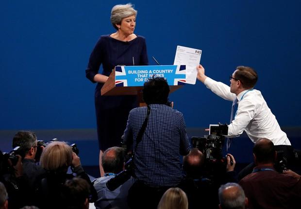 Comediante entrega formulário de demissão à primeira-ministra britânica, Theresa May, durante discurso, em Machester  (Foto: Phil Noble/Reuters)