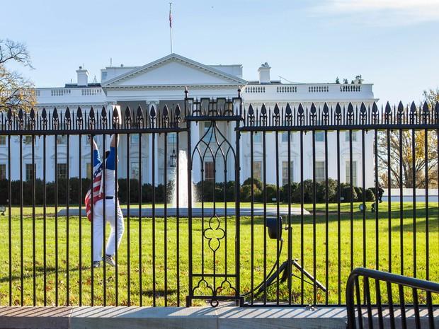 Foto fornecida por Vanessa Pena mostra o momento em que um homem coberto com uma bandeira americana pulou as grades da Casa Branca nesta quinta-feira (26) (Foto: Vanessa Pena via AP)