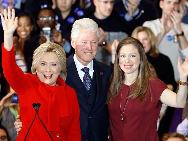 Hillary Clinton acena, ao lado do marido Bill e da filha Chelsea, após o caucus democrata em Iowa, na noite de segunda (1º) (Foto: AP Photo/Patrick Semansky)