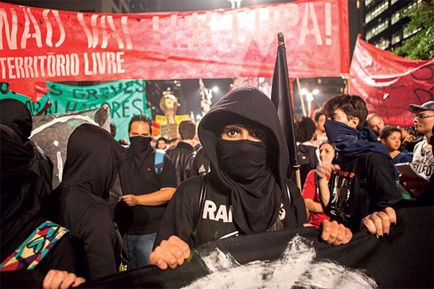 DO CONTRA Mascarados em protesto contra a Copa em São Paulo, na quinta-feira. A manifestação terminou com atos de vandalismo (Foto: Marcelo Min/Fotogarrafa/ÉPOCA)