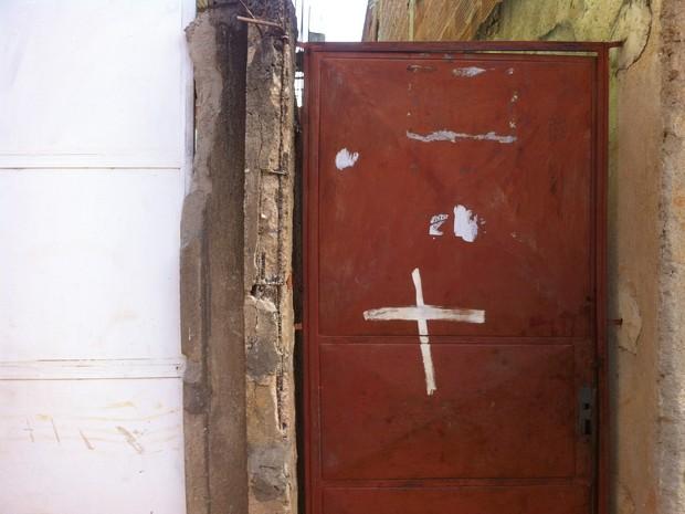 Corpos da mulher estava em uma escada, atrás desse portão. (Foto: Davidson Fortunato/G1)