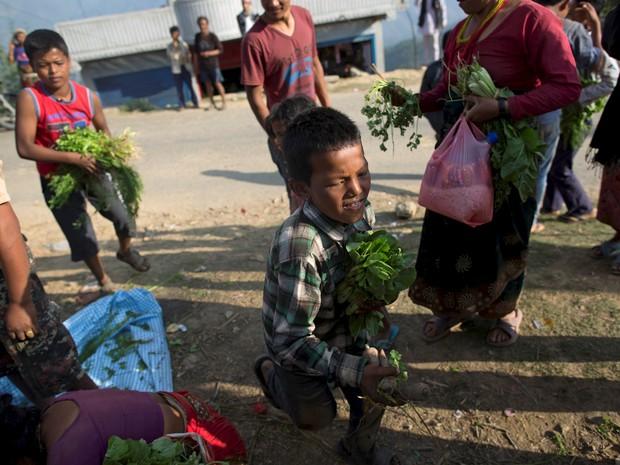 Garoto corre com legumes nas mãos, recebidos de um abrigo em  Sindhupalchowk (Foto: Reuters)
