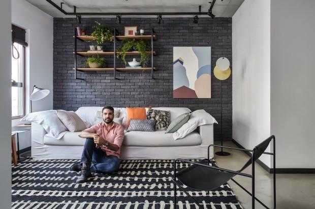 Bruno posa sobre o tapete da By Kamy, à frente do sofá da Espaço 204, com almofadas da JRJ Tecidos (Foto: Gui Morelli / Divulgação)