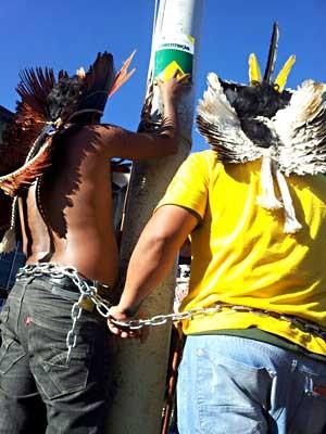 Índios exibem a Constituição enquanto estão acorrentados a poste (Foto: Vianey Bentes/TV Globo)