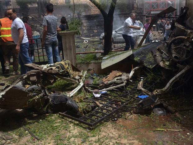 Bombeiros e moradores no local onde um projétil caiu e atingiu o hospital Dubeet, em Aleppo, no norte da Síria, na terça-feira (3) (Foto: SANA via AP)