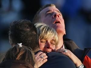 Pessoas choram diante da escola Sandy Hook (Foto: Reuters)