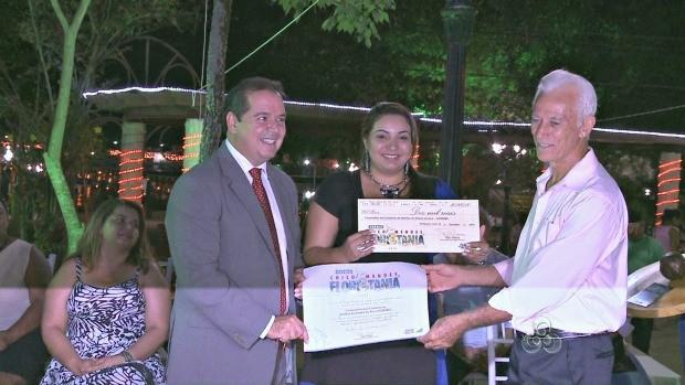 Premiado recebe das mãos do governador a gratificação (Foto: Acre TV)