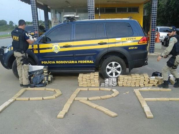Policiais descarregam droga encontrada em caminhão (Foto: PRF/Divulgação)
