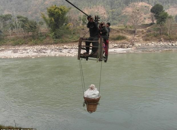 Pessoas carregam as compras no cesto até o outro lado do rio (Foto: Manish Duwadi / Barcroft India)