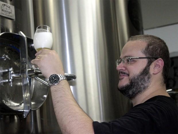 Walter Soares, da Guilda GIV, tra cerveja direto do tanque e avalia o líquido (Foto: Taiga Cazarine/G1)