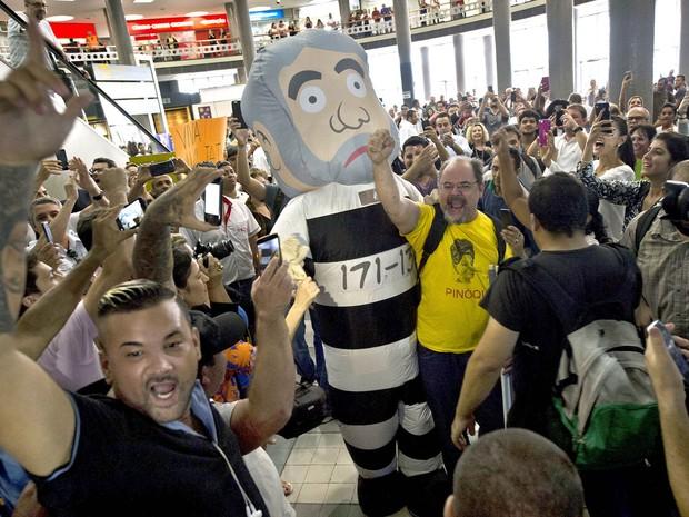 Manifestantes contrários ao ex-presidente Lula levaram um boneco réplica do inflável gigante apelidado de 'Pixuleco' para protestar no hall do Aeroporto de Congonhas, onde Lula estava sendo ouvido pela PF (Foto: Nelson Almeida/AFP)