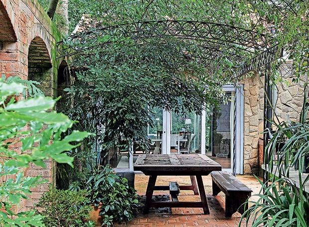 Ao lado da cozinha, o espaço é usado para tomar café e almoçar ao ar livre. Tutorada no pergolado de ferro, trepadeira jasmim-dospoetas. Em primeiro plano, do lado esq., leia-verde. À dir., íris-azul (Foto: Raphael Briest/Divulgação)