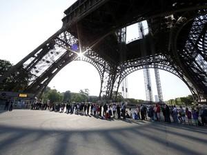 Turistas esperam em fila embaixo da Torre Eiffel, fechada pelo segundo dia por causa de greve (Foto: Gonzalo Fuentes/Reuters)