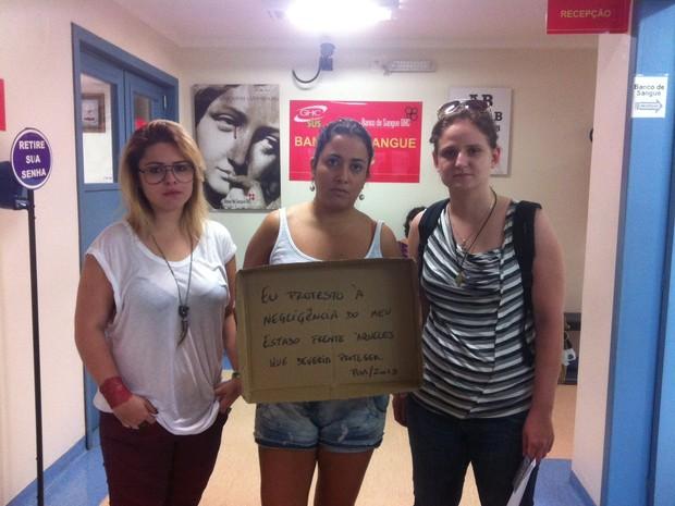 Iriane Kunz, Camila Moreira e Marina Rebelo protestaram com cartaz em hemocentro de Porto Alegre (Foto: Luiza Carneiro/ G1)