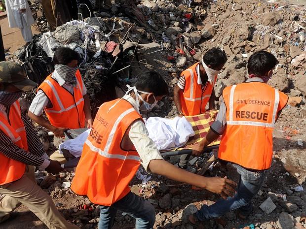 Equipe de resgate retira corpo dos escombros do prédio que ruiu na Índia na quinta-feira (4). (Foto: Indranil Mukherjee/AFP Photo)