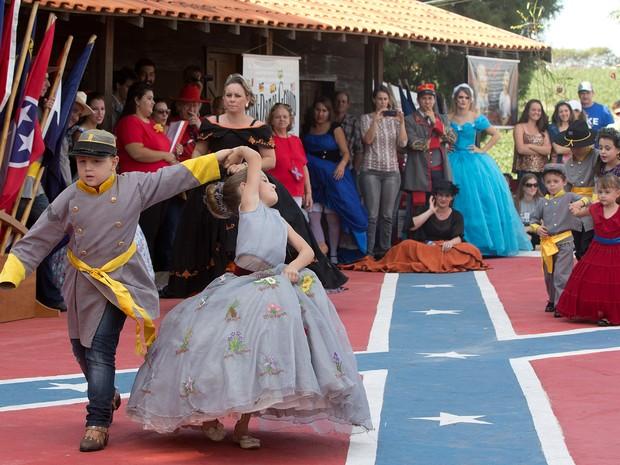 Crianças vestidas com uniformes e vestidos da Confederação dançam durante festa para comemorar o 150º aniversário do fim da Guerra Civil Americana em Santa Bárbara d' Oeste, no interior de São Paulo (Foto: Andre Penner/AP)