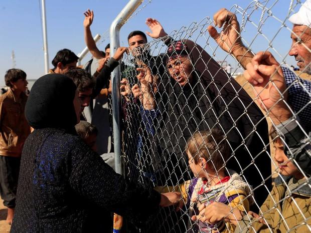 Iraquianos entram em contato com parentes que escaparam de Mossul na cerca do campo de refugiados de Al-Khazer  (Foto: Thaier Al-Sudaini/ Reuters)