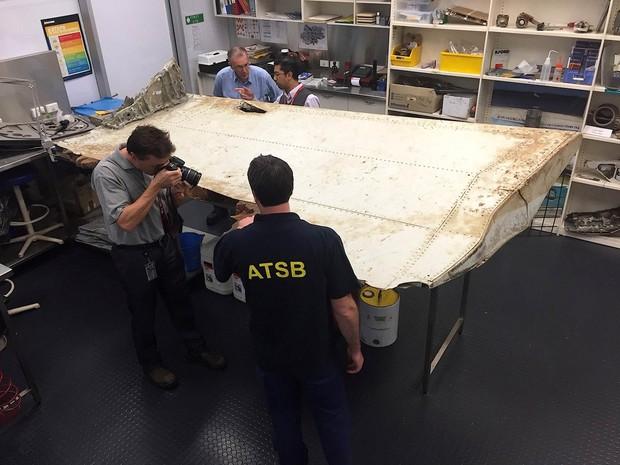 Equipes de investigação da Austrália e da Malásia examinam um destroço de avião na sede da autoridade australiana de segurança no transporte em Canberra. A peça foi achada na ilha Pemba, perto da Tanzânia, e pode ser do voo desaparecido MH370 da Malaysian (Foto: Reuters/Australian Transport Safety Bureau)