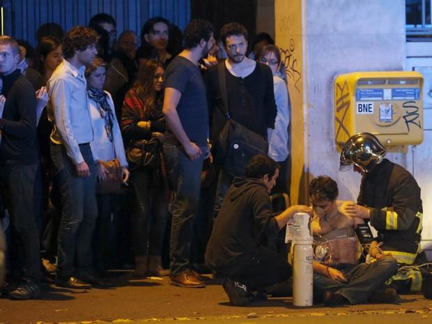 Homem é socorrido após tiroteio perto do Bataclan, conhecida sala de espetáculos de Paris, na França (Foto: Christian Hartmann/Reuters)
