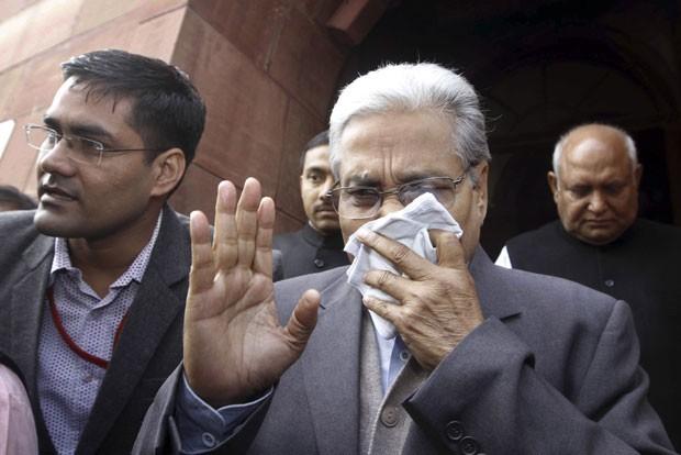 Parlamentar indiano protege o rosto após spray pimenta em sessão (Foto: AP)