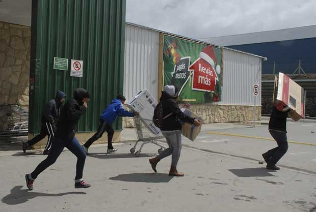 Pessoas correm com itens roubados de supermercado em Bariloche, Argentina, nesta quinta-feira (20) (Foto: AP)