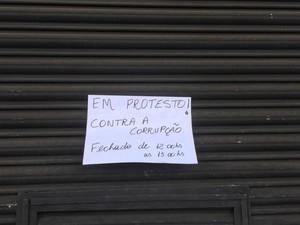 Comerciante baixa as portas e coloca cartaz em frente a loja em Campo Grande (Foto: Graziela Rezende)