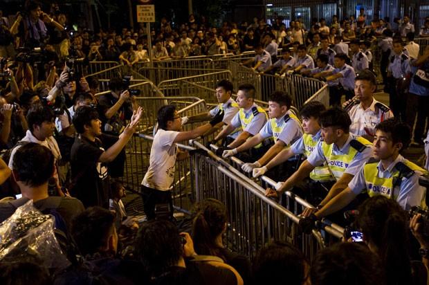 Policiais e manifestantes são vistos em frente ao legislativo de Hong Kong nesta quinta-feira (2), em mais um dia de protestos de estudantes por democracia (Foto: Xaume Olleros/AFP)