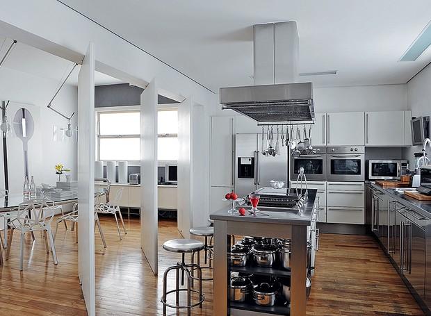 A cozinha tem a linguagem da arquiteta Valéria Blay, que gosta da neutralidade do branco, do preto e do prata. A sala de jantar pode ser isolada com portas pivotantes. Para facilitar, as panelas ficam em prateleiras abertas na ilha (Foto: Marcelo Magnani/Editora Globo)