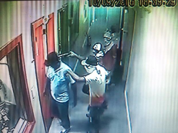 Na porta do estúdio, assaltantes apontam arma na cabeça do porteiro (Foto: Reprodução/TV Sergipe)
