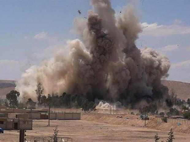 Imagem, divulgada no sábado (30), mostra fumaça sobre a prisão de Tadmur após prédio ser dinamitado pelo Estado Islâmico (Foto: Associated Press)