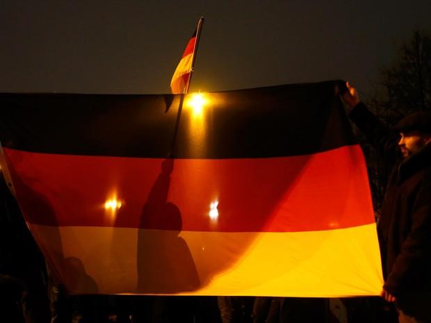 Participantes de um movimento popular ultra conservador contra muçulmanos seguram bandeiras alemãs durante uma manifestação em Berlim. Os manifestantes fazem parte do grupo Europeus Patrióticos contra a Islamização do Ocidente (PEGIDA, na sigla em inglês) (Foto: Hannibal Hanschke/Reuters)