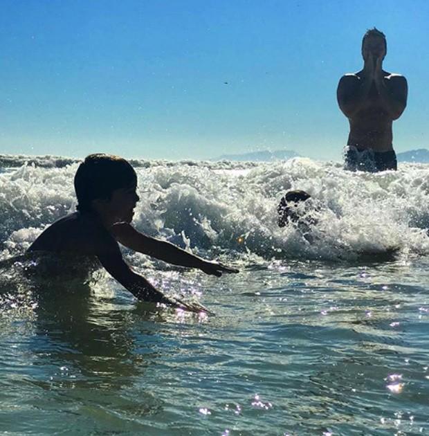 Carlos Eduardo Baptista observa filhos se divertindo no mar (Foto: Reprodução/Instagram)