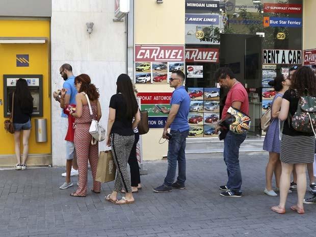 Pessoas fazem fila neste sábado (27) em caixa eletrônico da cidade de Iraklio, na ilha de Creta (Foto: REUTERS/Stefanos Rapanis)