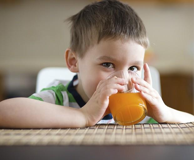 Little boy is drinking orange juice using straw (Foto: Getty Images/iStockphoto)