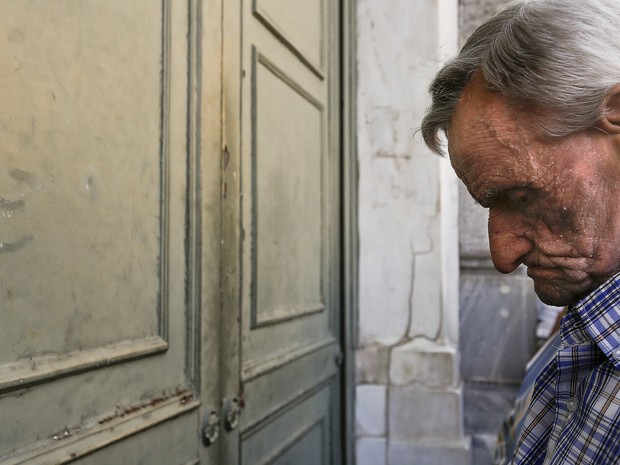 Aposentado aguarda em frente a banco fechado para receber benefício em Atenas, nesta terça (7) (Foto: Reuters/Yannis Behrakis)