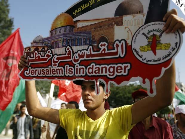 Homem segura cartaz onde se lê 'Jerusalém está em perigo' durante manifestação contra o controle de acesso a mesquita de Jerusalém (Foto:  AFP PHOTO/MOHAMMED ABED)