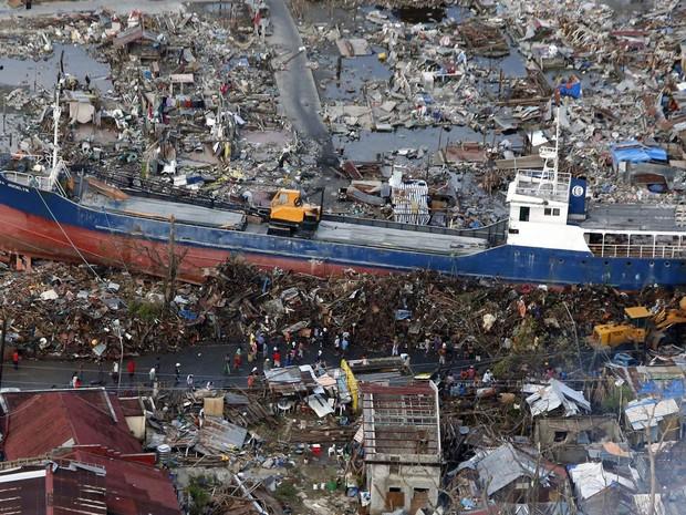 Filipinos passam por um navio arrastado para o meio de uma área residencial na passagem do tufão Haiyan quase duas semanas antes, no centro de Tacloban. (Foto: Erik de Castro/Reuters)