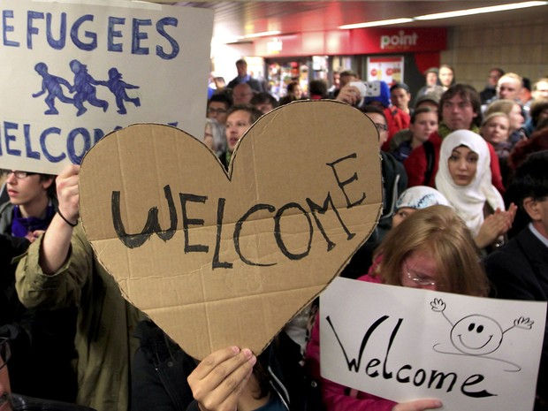 Grupo de refugiados é recebido com faixas de boas-vindas em estação ferroviária da Alemanha. (Foto: Ina Fassbende/Reuters)