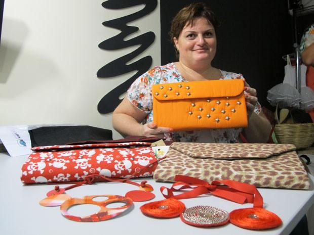Artesã exibe as bolsas e colares feitos de caixas de leite vazias (Foto: Mariane Rossi/G1)