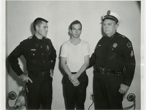 Lee Harvey Oswald, acusado de matar JFK, ao lado de policiais após ser preso no dia 22 de novembro de 1963 (Foto: Dallas Police Department/Dallas Municipal Archives/University of North Texas/Reuters)
