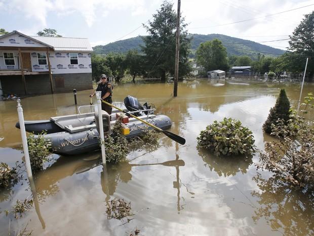 Autoridade passa de barco em área inundada em Rainelle, na Virgínia Ocidental, nos EUA, neste sábado (25) (Foto: Steve Helber/Reuters)