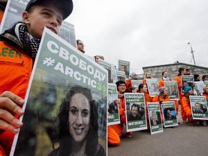 Ativistas do Greenpeace seguram cartazes com fotos de seus colegas presos, durante protesto neste sábado (5) em Moscou, capital da Rússia (Foto: AFP)