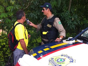 """O aposentado Nilo Raimundo """"sopra"""" o bafômetro e apoia ação fiscalizatória da polícia. (Foto: Diego Souza/G1)"""