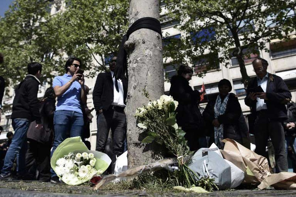 Flores foram deixadas no local onde policial foi morto na Avenida Champs Élysées, em Paris, na quinta-feira (21)  (Foto: Philippe Lopez / AFP)