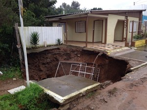 Força da chuva abre cratera em calçada ao lado de casa em Bagé, RS (Foto: Felipe Bastos/RBS TV)