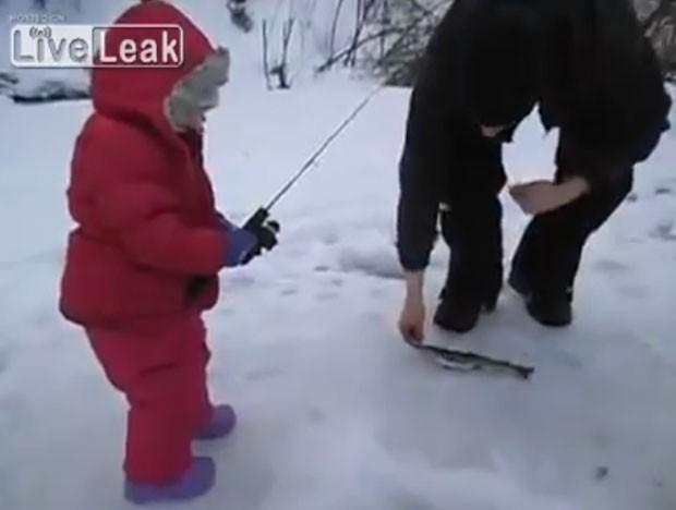 Criança teve dificuldades para puxar o peixe por pequeno buraco feito no gelo (Foto: Reprodução/LiveLeak/Your Daily Video)