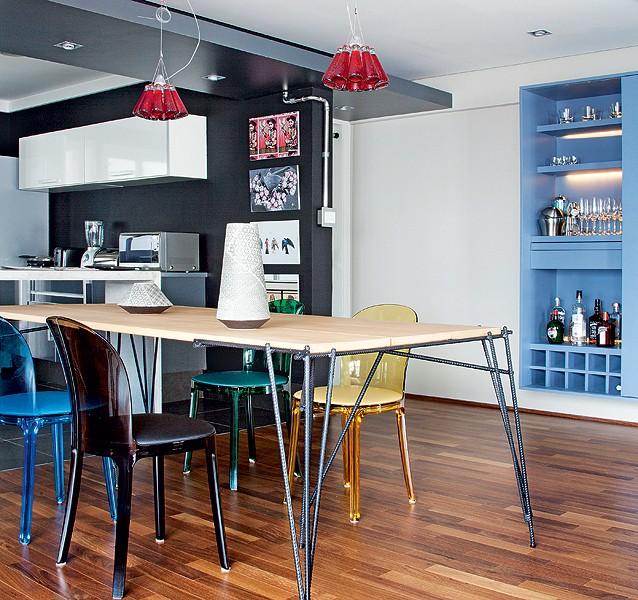 """As cadeiras Magis, em composição colorida, dão vida à sala de jantar. """"Adoro azul e cinza, mas, ao ir às compras, descobri que também gosto do amarelo"""", diz o morador Bruno Poppa. """"E o pendente de garrafinhas de Campari deu um ar divertido"""", completa (Foto: Maíra Acayaba/Casa e Jardim)"""