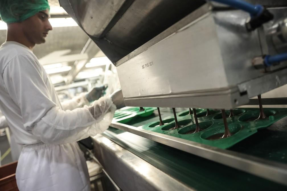 Chocolate é despejado nos moldes para se transfomar em ovos de Páscoa (Foto: Fábio Tito/G1)