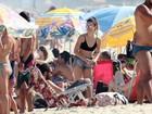 Bianca Bin curte praia e passa protetor solar no marido
